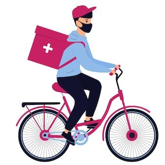 Doręczyciel w masce ochronnej dostarcza lekarstwa rowerem
