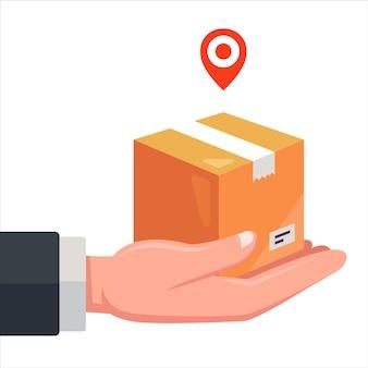 Dostawa przesyłek kurierem. trzymaj w dłoni kartonowe pudełko.