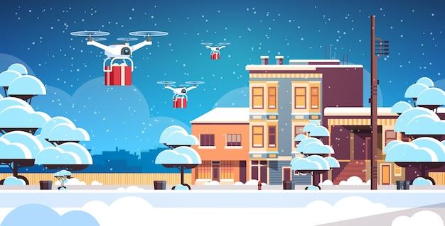 Dostawy drony przewożące prezent pudełka wesołych świąt szczęśliwego nowego roku zimowe wakacje koncepcja poczta lotnicza nowoczesne zaśnieżone miasto ulica pejzaż poziomy ilustracji wektorowych