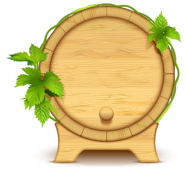 Drewniana beczka na wino i piwo. zielone liście chmielu na beczce