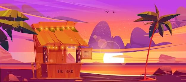 Drewniana chata tiki bar z napojami i przekąskami w maskach plemiennych na plaży o zachodzie słońca