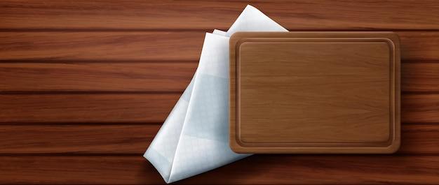Drewniana deska do krojenia stoi na serwetce kuchennej i powierzchni stołu z drewna, widok z góry