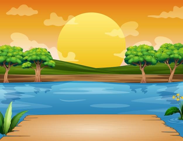Drewniana ławka z widokiem na rzekę i zachód słońca