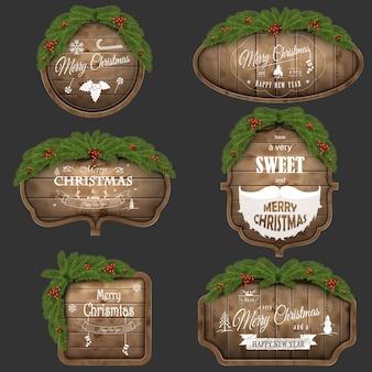 Drewniana tablica świąteczna z gałęziami sosny i świątecznymi życzeniami.