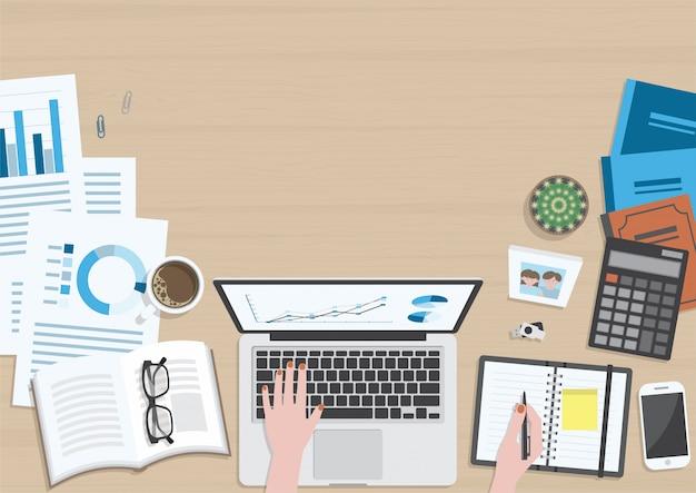 Drewniane biurko z góry widok z rąk kobiety pracującej na komputerze przenośnym i materiały biurowe