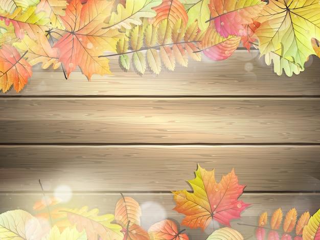 Drewniane deski z jesiennymi liśćmi.