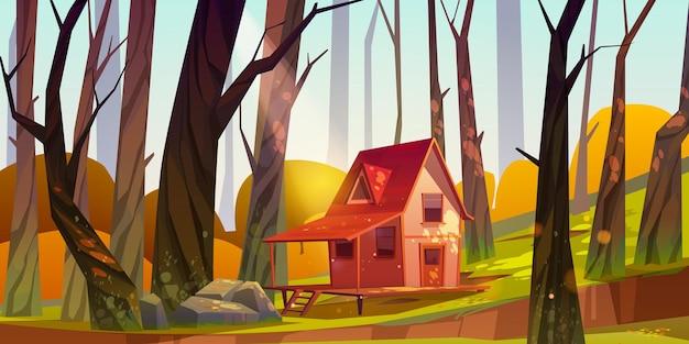 Drewniany dom na palach w lesie jesienią.