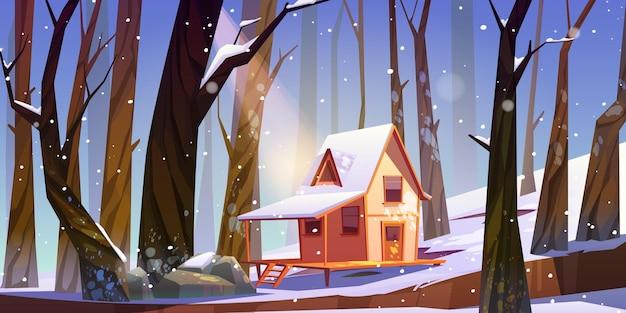 Drewniany dom na palach w zimowym lesie.