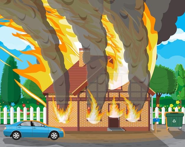 Drewniany dom płonie. ogień w domku. pomarańczowe płomienie w oknach, czarny dym z iskrami. ubezpieczenie mienia. krajobraz przyrody. koncepcja klęski żywiołowej.