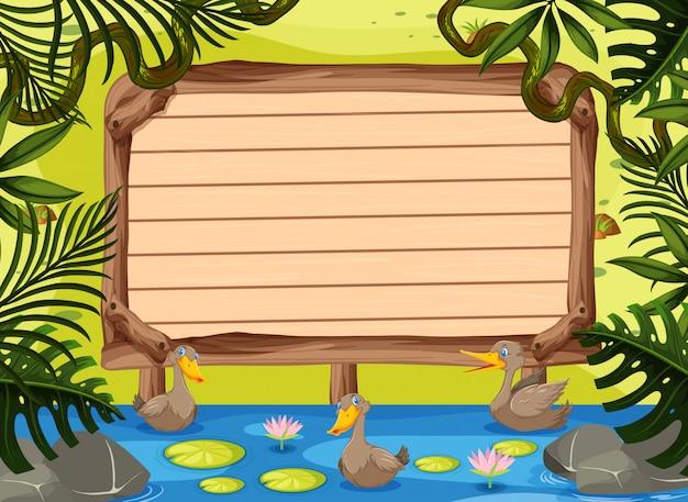 Drewniany szyldowy szablon z kaczkami pływa w rzece