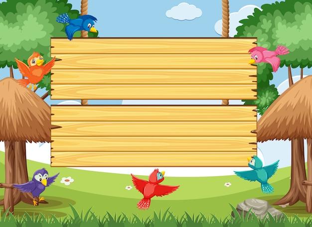 Drewniany szyldowy szablon z kolorowymi ptakami lata w parku