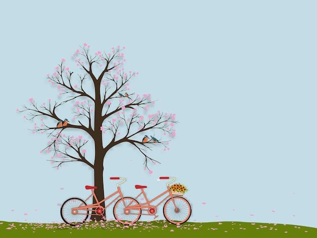 Drzewo z ptakiem zimorodka stojącym na gałęziach, rower, liście różowego serca spadające na ziemię.