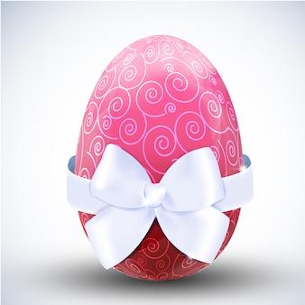 Duże wzorzyste różowe szczęśliwe jajko wielkanocne z ikoną kokardki jedwabnej wstążki na jasnej powierzchni realistycznej ilustracji wektorowych