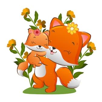 Duży lis podnosi małego lisa w ogrodzie z jasnymi kwiatami ilustracji