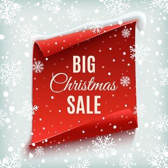 Duży plakat sprzedaży świątecznej. czerwony, zakrzywiony, papierowy baner na tle zimy ze śniegiem i płatkami śniegu.