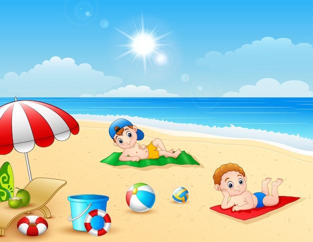 Dwa chłopiec sunbathing na plażowej macie