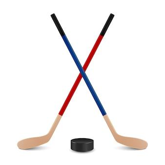Dwa skrzyżowane kije hokejowe - czerwony i niebieski - oraz krążek. na białym tle