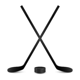 Dwa skrzyżowane kije hokejowe i krążek hokejowy. pojedynczo na białym backgrund.