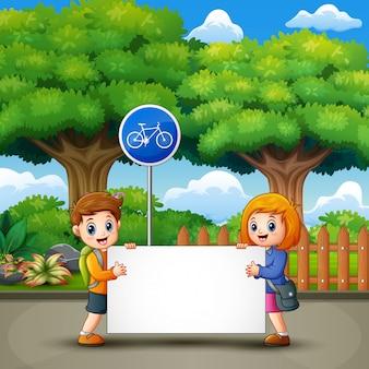 Dwa słodkie dzieci trzymają transparent w parku miejskim