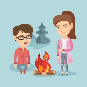 Dwaj przyjaciele siedzą przy ognisku na kempingu.