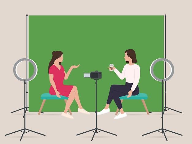 Dwie damskie transmisje na żywo w domowym studiu z profesjonalnym sprzętem zielony ekran aparatu dslr w pierścieniu światła