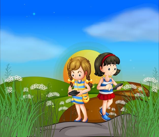 Dwie dziewczyny na wzgórzu za pomocą swoich telefonów komórkowych