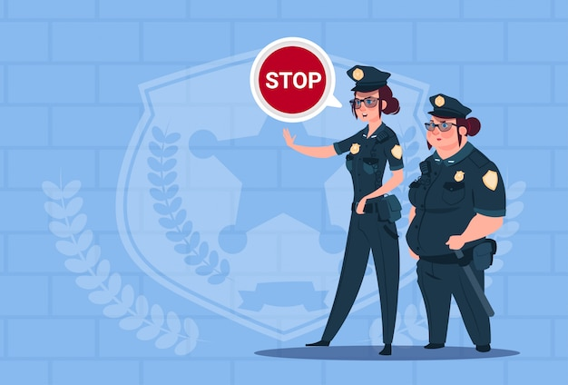 Dwie kobiety policji gospodarstwa znak stop noszenia mundurowych strażników kobiet na niebieskim tle cegieł