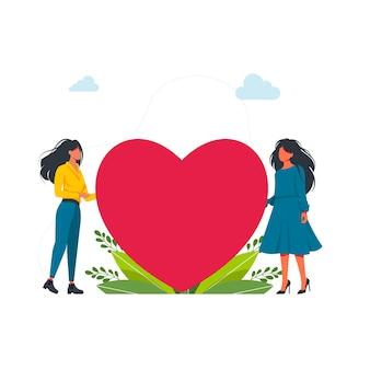 Dwie kobiety posiadające wielkie serce. lgbt, miłość to miłość, miesiąc szczęśliwej dumy. pewne siebie dziewczyny wspierają się nawzajem. dwie płaskie samice siedzące w pobliżu dużego czerwonego serca. akceptacja siebie. ilustracja wektorowa