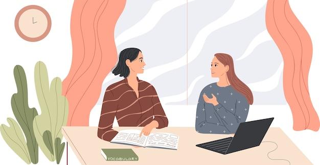 Dwie kobiety siedzą przy biurku i rozmawiają.