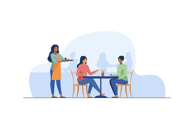 Dwie kobiety siedzą w kawiarni.