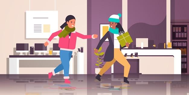 Dwie kupujące kobiety walczące o ostatnie pudełko prezentowe mieszają wściekłych klientów w walce o sezonowe zakupy