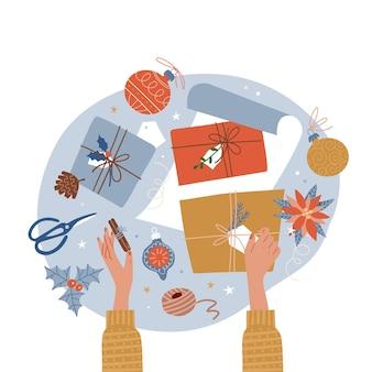 Dwie ręce owijające stylowe pudełko na prezenty świąteczne w jasny papier i gałęzie sosnowe owijające świąteczną...
