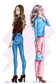 Dwie stylowe piękne kobiety w modnych ubraniach