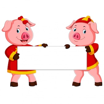 Dwie urocze świnki trzymają białą deskę na chiński nowy rok