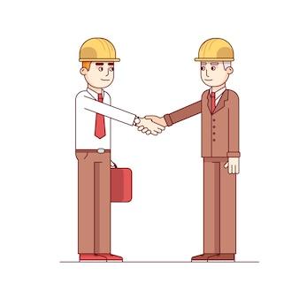 Dwóch architektów lub inżynierów budowlanych uścisk dłoni