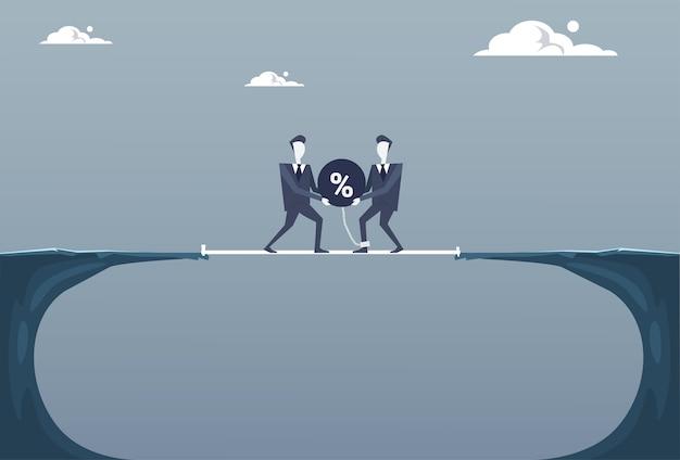 Dwóch biznesmenów rzucanie procent piłkę w klifie