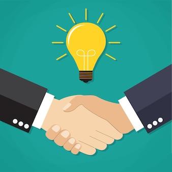Dwóch biznesmenów uściska dłonie, aby uzyskać umowę