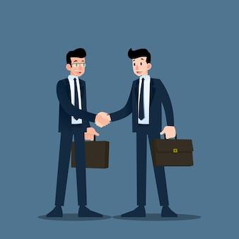 Dwóch biznesmenów uścisnąć sobie ręce.