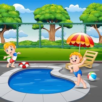 Dwóch chłopców biegających na brzegu basenu w ogrodzie