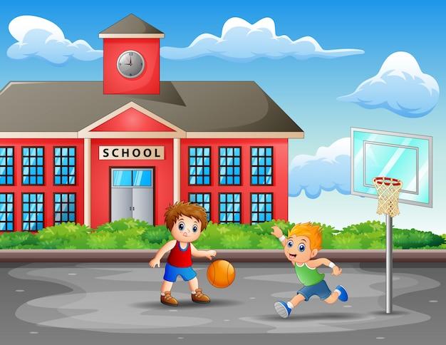 Dwóch chłopców grających w koszykówkę na dworze