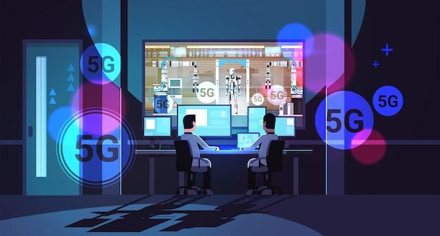 Dwóch inżynierów obserwujących monitory produkcji robotów nowoczesna fabryka robotów 5g koncepcja bezprzewodowego połączenia online