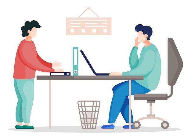 Dwóch komunikujących się kolegów w biurze siedzi przy stole z laptopem i na stojąco