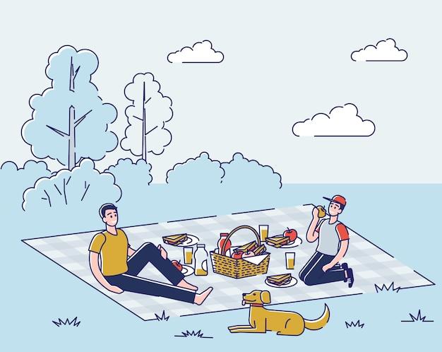 Dwóch młodych chłopców przyjaciół z psem siedzi na kocu, jedzenie na świeżym powietrzu na wakacje lub w weekend
