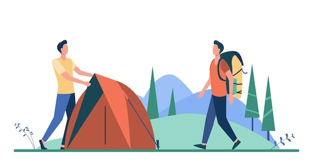 Dwóch turystów rozbija namiot na łące.