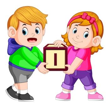 Dwoje dzieci niosących alfabet blok