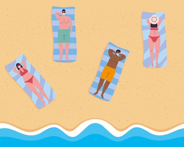 Dystans społeczny na plaży, ludzie noszący maskę medyczną leżący opalający się, zachowanie dystansu, nowa koncepcja normalnej letniej plaży po koronawirusie lub covid 19