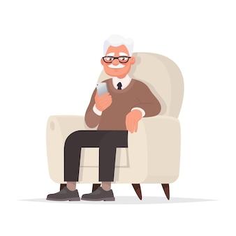 Dziadek siedzi na krześle i trzyma w ręku telefon.