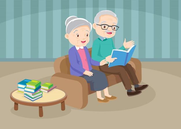Dziadek z babcia czytanie książki razem na kanapie