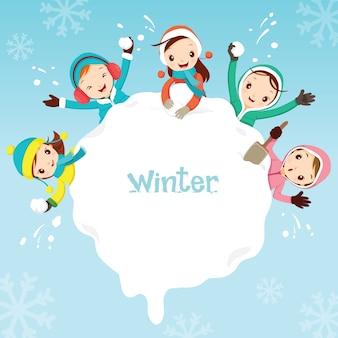 Dzieci bawią się razem śniegiem wokół zaspy śnieżnej