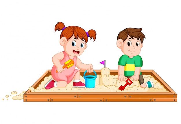 Dzieci bawią się szczęśliwie w piasku